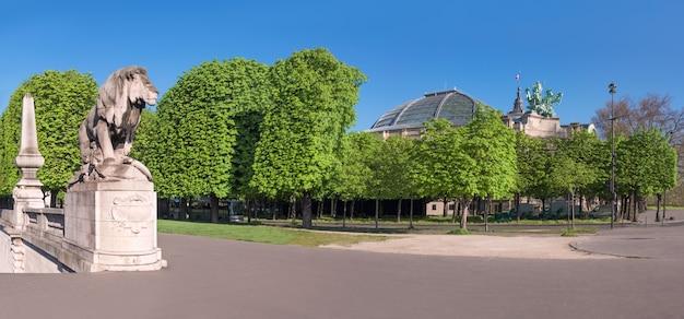 Löwestatue und großartiges palais in paris im frühjahr