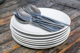 Löffel und Gabeln auf Stapel Platten auf Holztisch