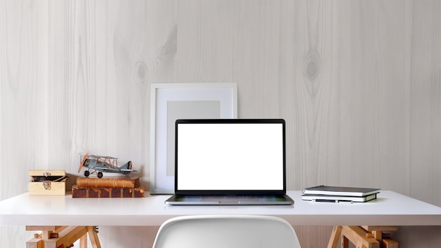 Loftarbeitsplatz mit laptop und plakat des leeren bildschirms auf weißem schreibtisch.