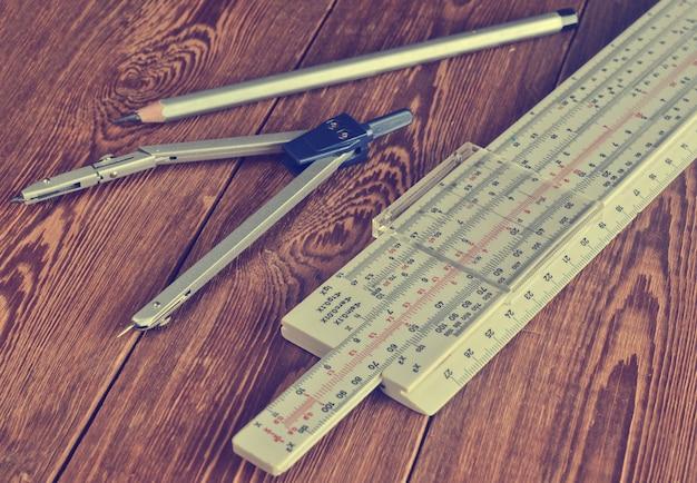 Logarithmisches lineal, kompass, bleistift auf einem holztisch.