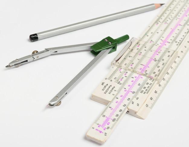 Logarithmisches lineal, kompass, bleistift auf weiß