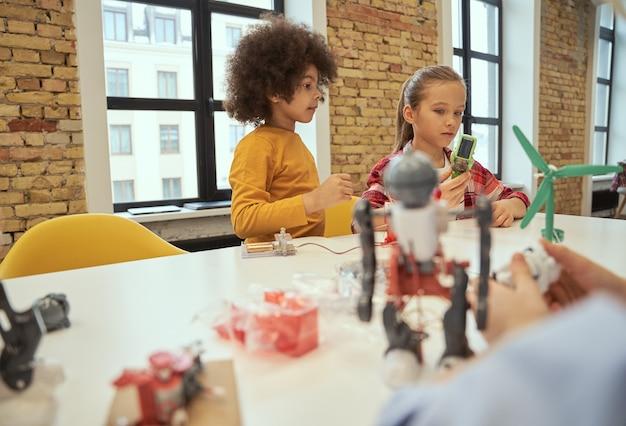 Logische analyse süßer kleiner junge und mädchen, die roboter während des stammunterrichts herstellen