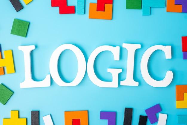 Logischer text mit bunten holzpuzzleteilen, geometrischer formblock auf blauem hintergrund. konzepte des logischen denkens, rätsel, lösungen, rationalität, strategie, welttag der logik und bildung