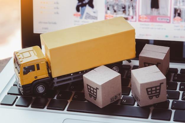 Logistik und lieferservice - lkw- und papierkartons oder pakete mit einem einkaufswagenlogo auf einer laptoptastatur. einkaufsservice im online-web und bietet lieferung nach hause.
