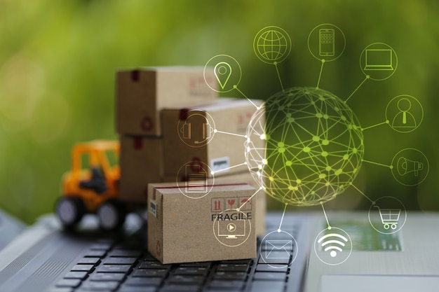 Logistik-, versorgungs- / online-einkaufskonzept: gabelstapler bewegt pappkarton auf tastatur mit symbol kundennetzwerkverbindung. internationaler fracht- oder versandservice für online-einkäufe.