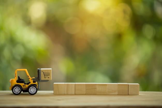 Logistisches netzwerkverteilung und frachtfrachtkonzept: mini-gabelstapler bewegt eine palette mit holzblock mit symbol. zeigt die lieferung von waren oder produkten rund um den globus im e-commerce.