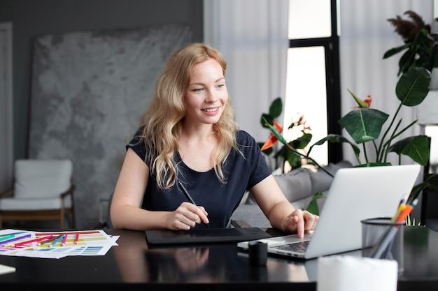 Logodesignerin, die an ihrem tablet arbeitet, das mit einem laptop verbunden ist