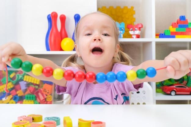 Logopädie, die entwicklung der feinmotorik. kleinkindmädchen reiht perlen an einer schnur auf.