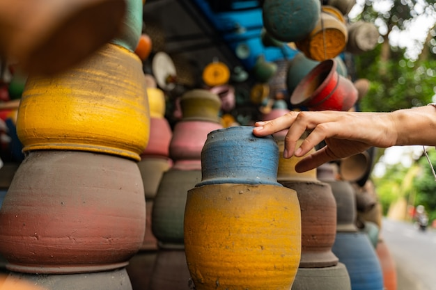 Lokale keramik. junge weibliche person, die ihre hand ausdehnt, während sie blauen topf für sich kauft buy