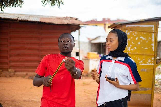 Lokaler afrikanischer tischler bei der arbeit, der seinem kunden erklärt
