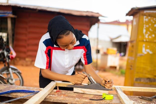 Lokaler afrikanischer tischler bei der arbeit lächelnd