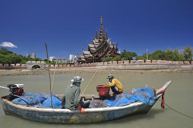 Lokaler fischer mit traditionsboot am schongebiet der wahrheit in pattaya, thailand.