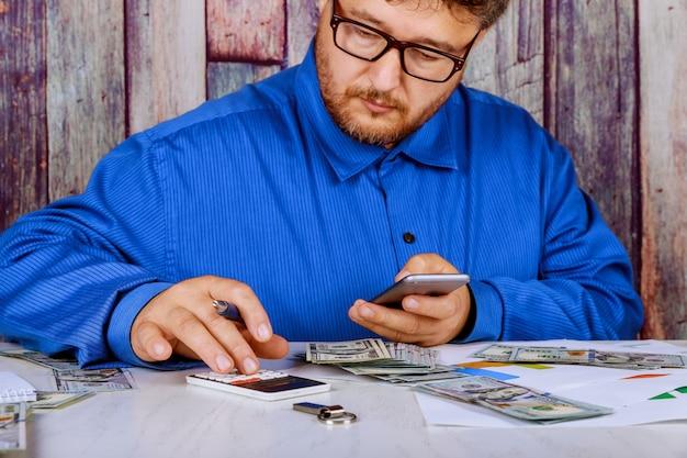 Lokaler geschäftsmann unter verwendung des taschenrechners des gesamtpreises von gezahlt durch us-dollar rechnungen