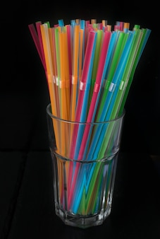 Lokalisierte gruppe plastikfarbstrohe in einem glas auf einem schwarzen hintergrund. sommer, festivalausstattung.