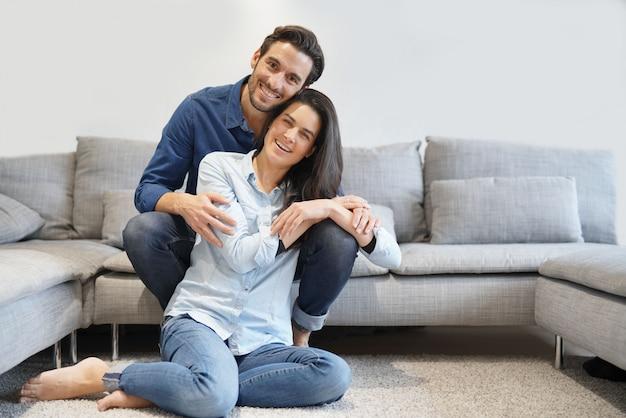 Lokalisierte herrliche lächelnde paare im denim auf bequemer couch