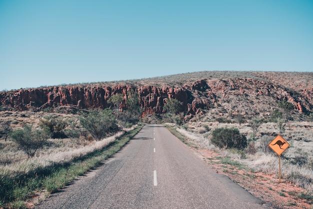 Lokalisierte und einsame straße in der roten mitte im australischen hinterland