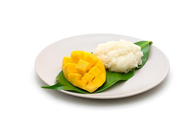 Lokalisierter teller von schnitzen schöne gelbe mango mit klebrigem reis auf weiß