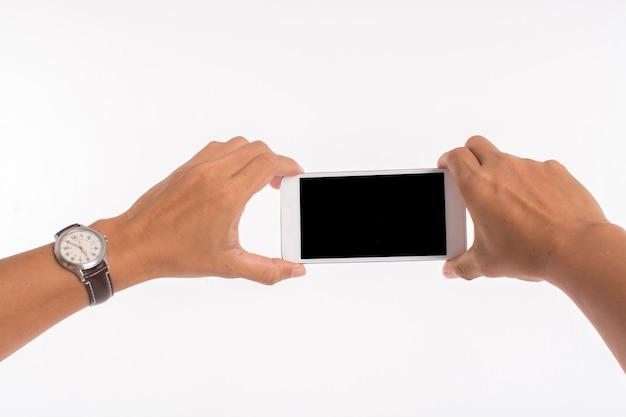 Lokalisiertes bild von den händen, die handy halten und foto auf weiß machen