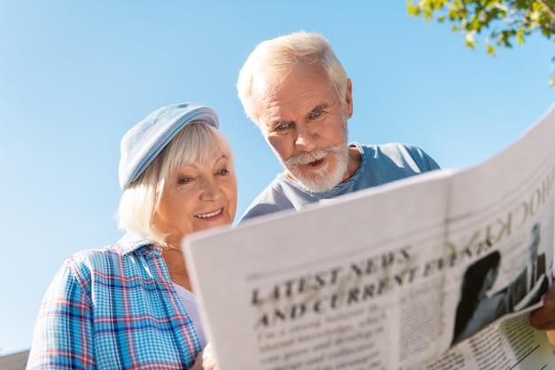 Lokalnachrichten. älteres ehepaar, das sich wirklich engagiert und aufgeregt fühlt, während es morgens vor dem haus lokale nachrichten liest