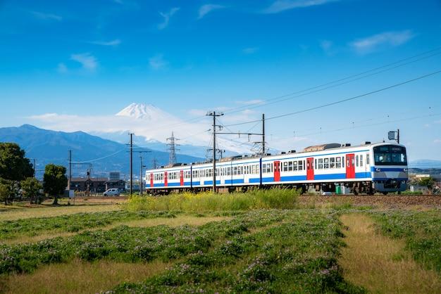 Lokalzug der jr izuhakone tetsudo-sunzu-linie, die an einem sonnigen frühlingstag durch die landschaft fährt