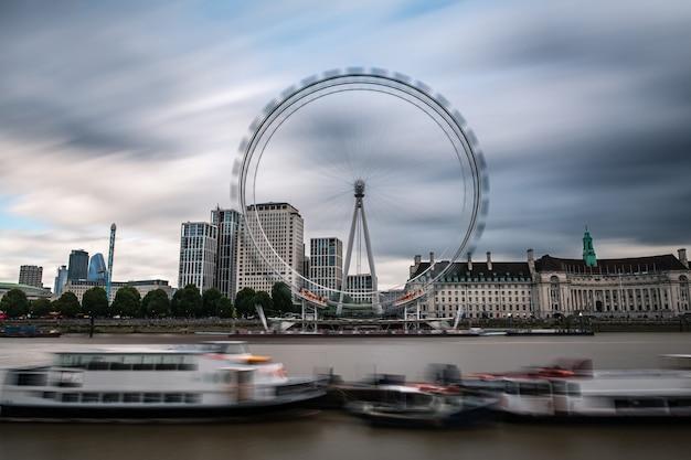Londoner stadtbild an der themse mit dem millennium wheel an einem grauen regnerischen sommertag.