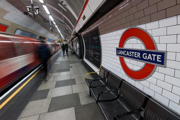 Londoner u-bahn-zeichen mit fahrendem zug und menschen an der lancaster gate station