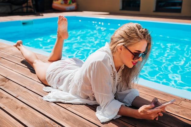 Long shot blonde frau, die ihr telefon überprüft