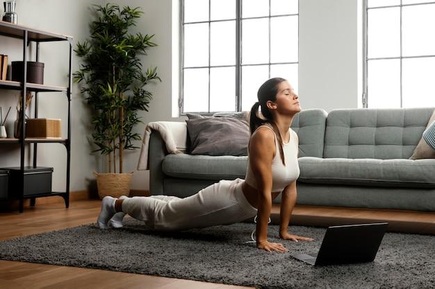 Long shot der frau, die yoga praktiziert