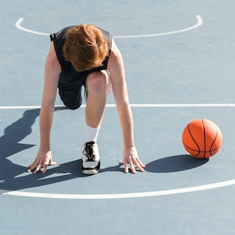 Long shot des jungen mit basketballball
