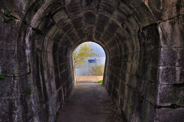 Long shot eines gewölbten ziegelsteintunnels mit blick auf einen see mit einem boot am gegenüberliegenden ende