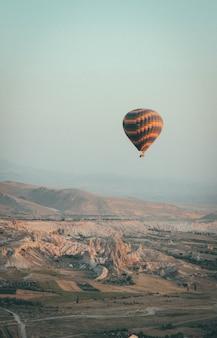 Long shot eines mehrfarbigen heißluftballons, der im himmel hoch über den bergen schwebt