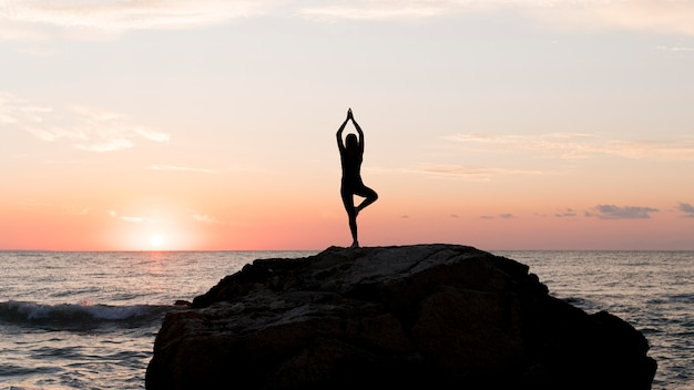 Long shot frau in sportbekleidung meditiert auf einem felsen