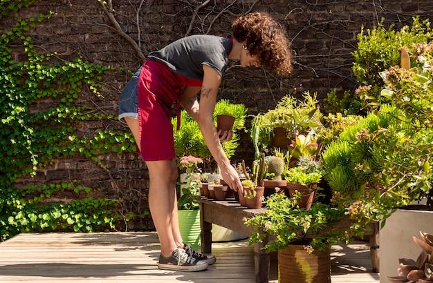 Long shot frau kümmert sich um ihre pflanzen