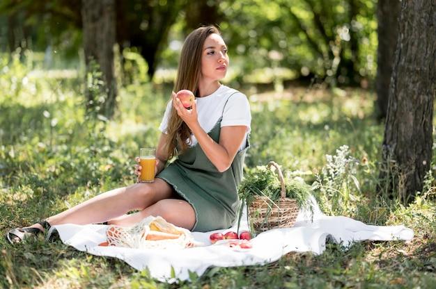 Long shot frau mit einem picknick mit gesunden snacks