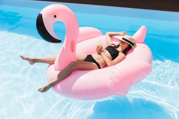 Long shot girl, das auf flamingo floatie niederlegt