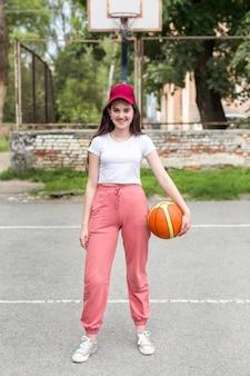 Long shot junges mädchen hält einen basketball