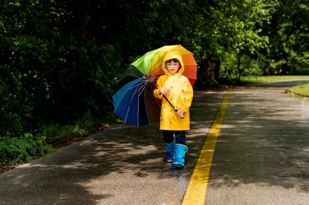 Long shot kleiner junge hält einen regenschirm über dem kopf