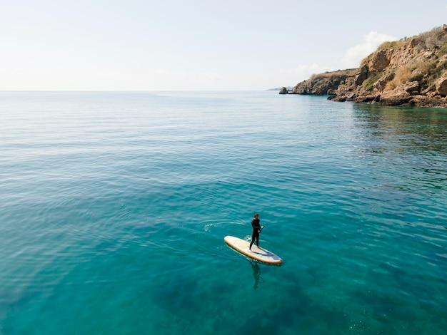 Long shot mann beim surfen mit schöner aussicht