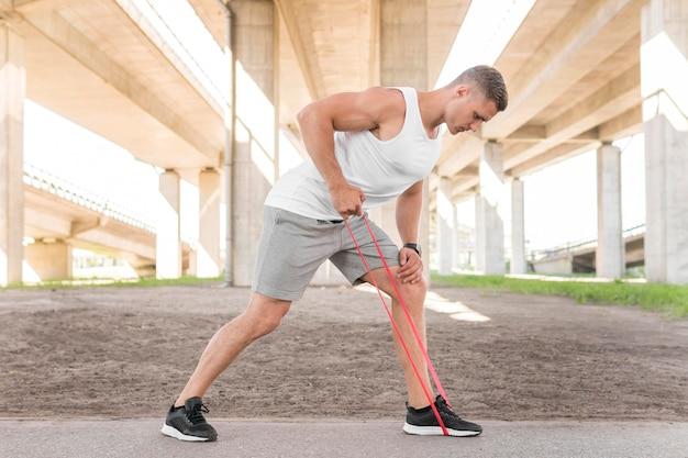 Long shot mann trainiert mit einem roten stretching band