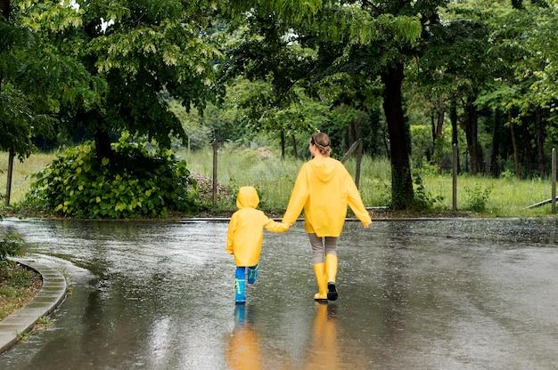Long shot mutter und sohn händchen haltend beim tragen von regenmänteln
