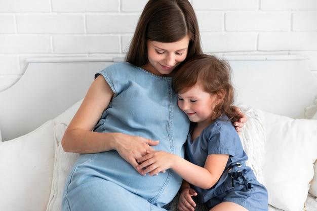 Long shot schwangere mutter und tochter im schlafzimmer bleiben