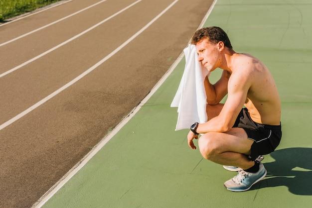 Long shot von bodybuilder schweiß abwischen