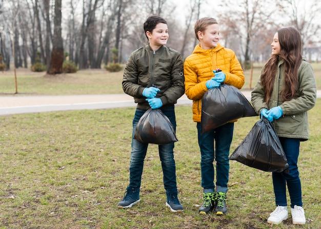 Long shot von kindern, die plastiktüten halten