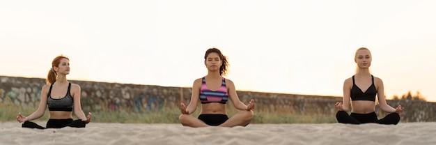 Long shot von mädchen, die am strand meditieren