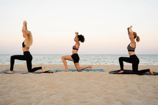 Long shot von mädchen, die am strand trainieren