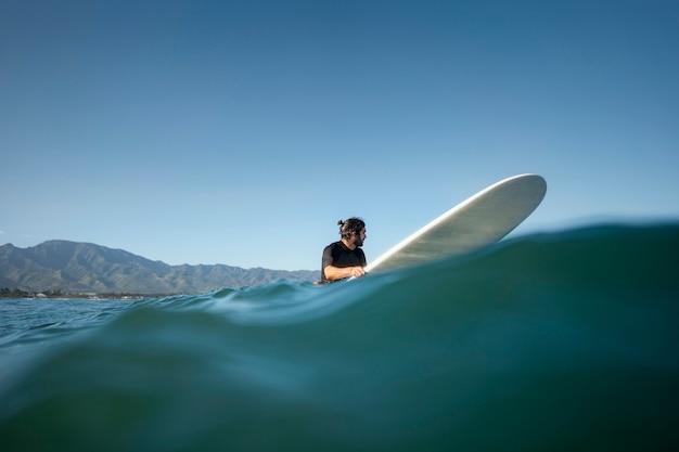 Long shot von mann auf seinem surfbrett