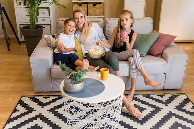 Long shot von mutter und ihren kindern im wohnzimmer sitzen