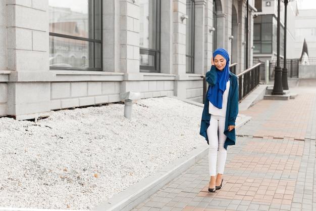 Long shot wunderschönes mädchen mit hijab lächelnd