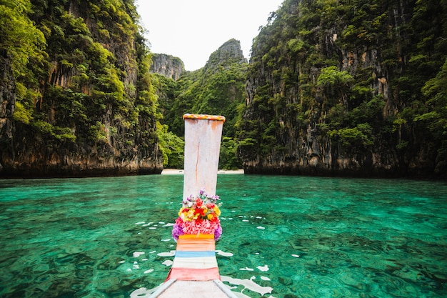 Long-tail-boot schwimmt im transparenten wasser der phi-phi-insel, maya bay, der paradiesinsel in thailand.