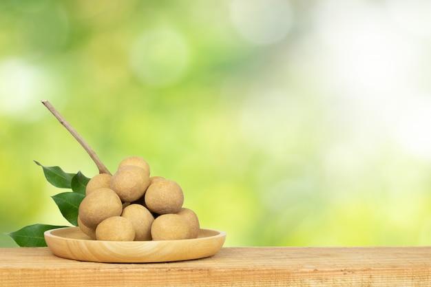 Longanfrucht auf tabelle und grünem natur blurlight hintergrund